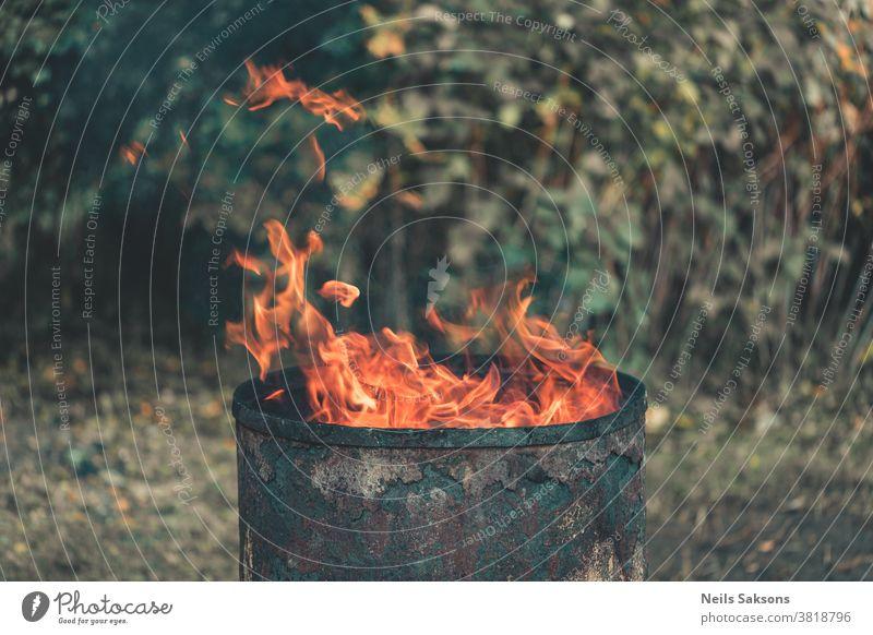 Feuer im Gartenkamin aus einem alten Metallfass Lauf Behälter verbrannt Dose Container Gefahr Zerstörung Müllhalde Flamme Trödel Abfall Verschmutzung Sicherheit