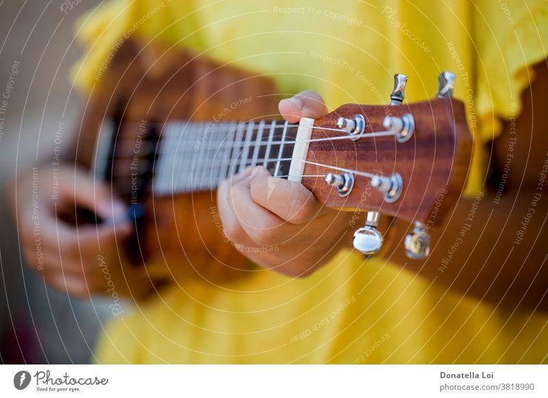 Nahaufnahme eines Mädchens mit Ukulele Künstler Differential-Fokus Finger Hände Instrument Lifestyle Melodie Musik Musical Musiker im Freien Person spielen
