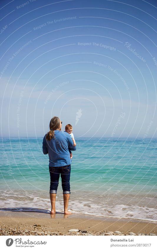 Vater und Sohn am Strand Baby Barfuß Windstille Kind Kindheit Textfreiraum Tag tagsüber von hinten Beteiligung kleiner Junge auf das Meer schauen Mann Natur
