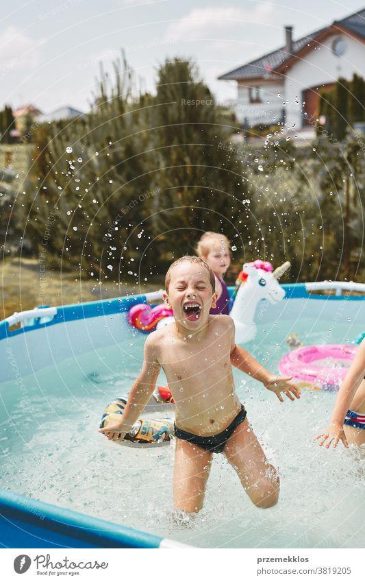 Junge springt und planscht in einem Pool authentisch Hinterhof Kindheit Kinder Familie Spaß Garten Fröhlichkeit Glück Freude Lachen Lifestyle spielerisch