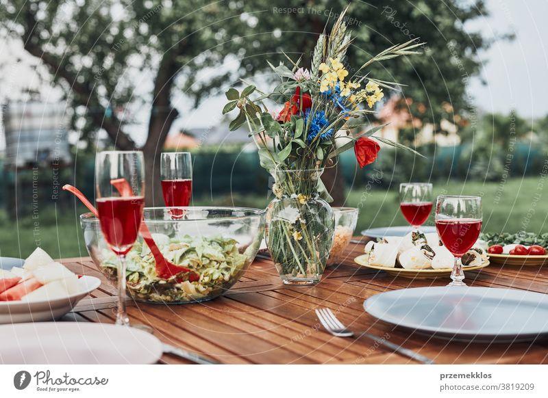 Abendessen in einem Apfelgarten auf einem Holztisch mit Salaten und Wein, dekoriert mit Blumen heimwärts Festessen Picknick Lebensmittel Sommer Barbecue Tisch