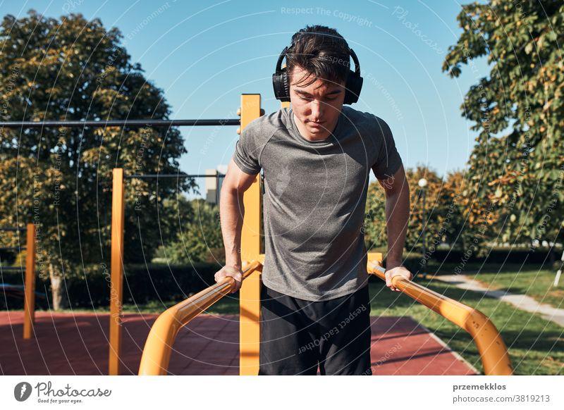 Junger Mann, der während seines Trainings in einem modernen Gymnastikpark auf parallelen Stangen baden geht calisthenics Pflege Kaukasier Gesundheit Lifestyle