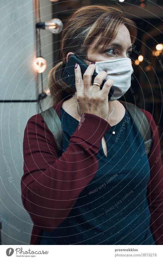 Junge Frau, die vor einem Restaurant in der Innenstadt telefoniert und die Gesichtsmaske trägt, um eine Virusinfektion zu vermeiden Anruf Pflege Kaukasier