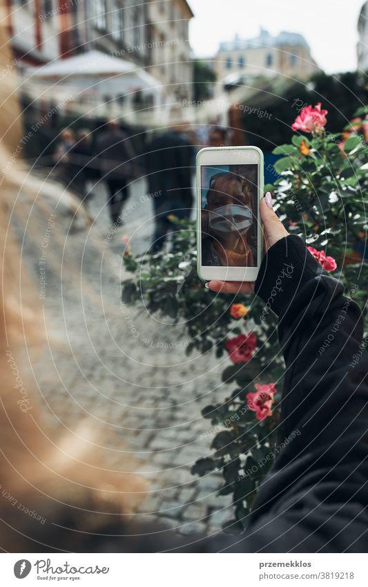 Junge Frau mit Videogesprächen, die abends auf einem Spaziergang durch die Innenstadt mit der Gesichtsmaske spricht, um eine Virusinfektion zu vermeiden Anruf