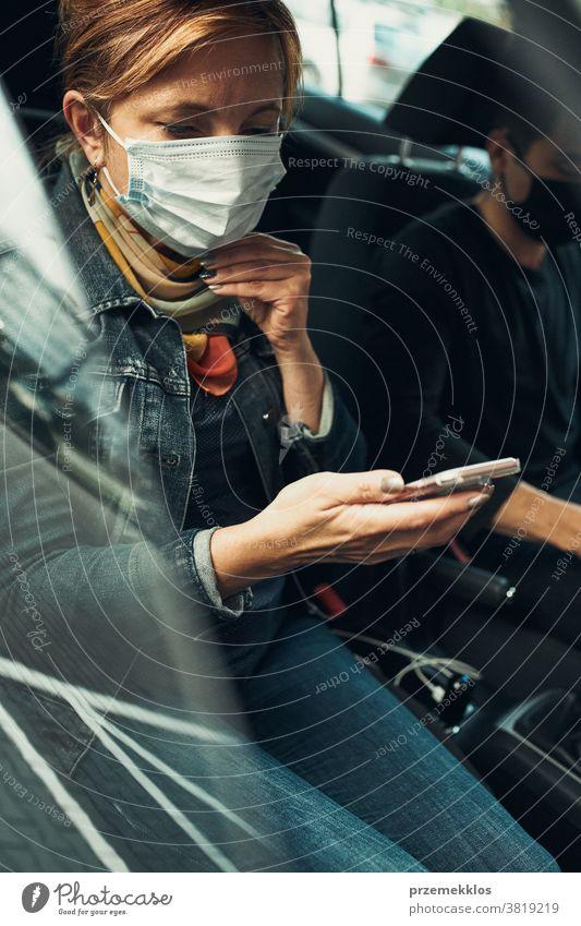 Frau, die mit einem Smartphone telefoniert und mit der Gesichtsmaske in einem Auto sitzt, um eine Virusinfektion zu vermeiden Kaukasier covid-19 Lifestyle