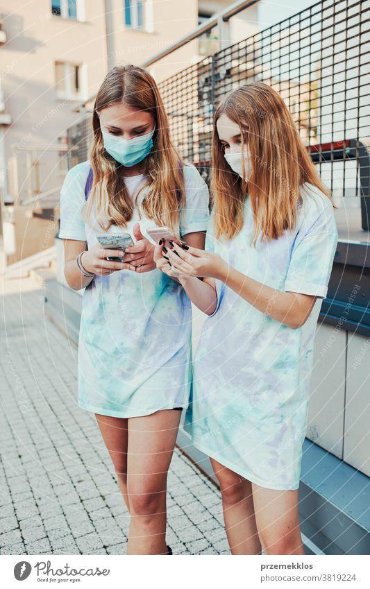 Junge Frauen, die Smartphones benutzen und die Gesichtsmasken tragen, um eine Virusinfektion zu vermeiden, wenn sie auf der Straße stehen Kaukasier Funktelefon