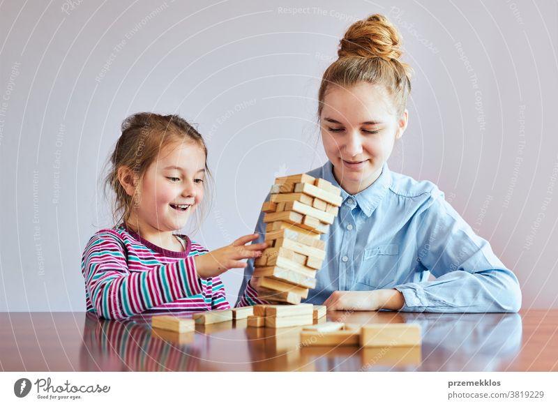 Kleines Mädchen im Vorschulalter und ihre ältere Schwester spielen zusammen mit Holzklötzen Spielzeug Aktivität Klotz Blöcke Baustein bauen Kind Kindheit