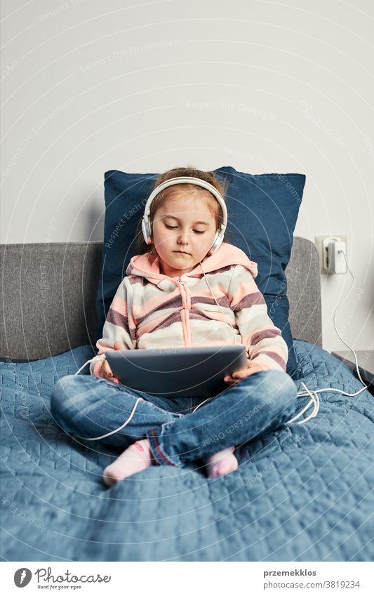Kleines Mädchen im Vorschulalter lernt online Rätsel lösen und spielt zu Hause Lernspiele auf Tablet Bett Schlafzimmer Kaukasier Kind Kindheit Computer niedlich