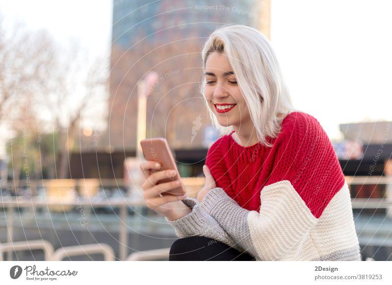 Nahaufnahme eines Porträts einer schönen jungen Frau, die ein Mobiltelefon im Freien in der Stadt benutzt Smartphone 1 Lächeln Beteiligung Fröhlichkeit Stehen