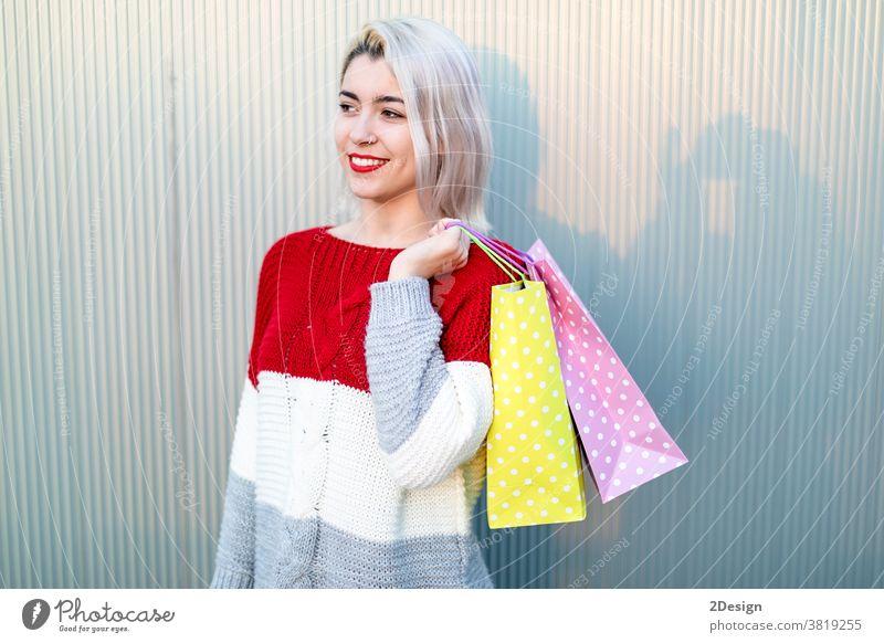 Porträt einer jungen, glücklich lächelnden Frau mit Einkaufstaschen Stehen 1 kaufen Tasche Käufer Fröhlichkeit schön Kauf Mädchen konsumgeil Lächeln Person