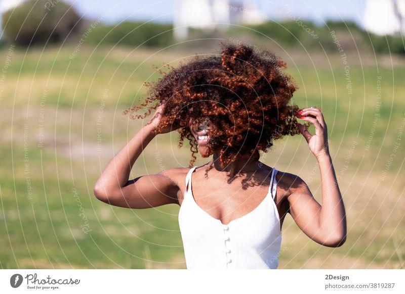 Schöne afroamerikanische Frau in weißem Kleid, die an einem sonnigen Tag im Gras in einem Park sitzt. Sitzen Afro-Look 1 Afroamerikaner jung Porträt im Freien