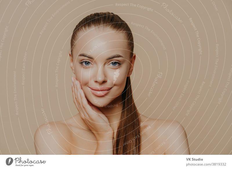 Foto einer hübschen jungen Frau mit glatter, gesunder Haut nach Schönheitsbehandlungen und Gesichtsmassage, steht nackt auf den Schultern, hat langes, dunkles, glattes Haar, isoliert über einer beigen Wand, die ihren Körper pflegt