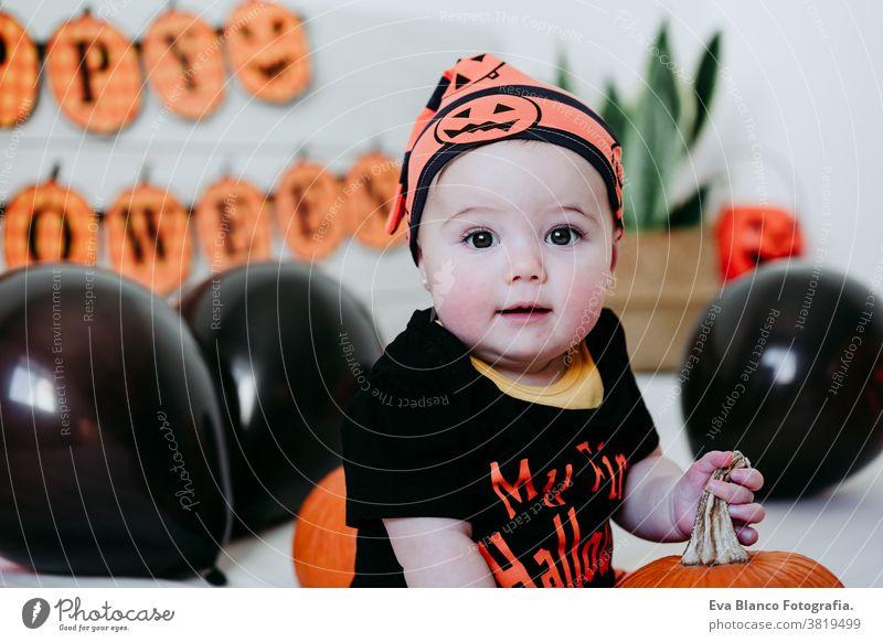 süßes kleines Mädchen in Halloween-Kostüm zu Hause, auf dem Bett sitzend mit Halloween-Dekoration, Lifestyle drinnen Tracht heimwärts im Innenbereich