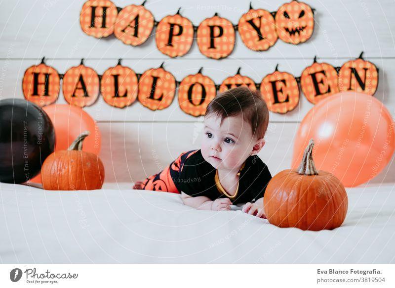niedlichen Baby-Mädchen in halloween-Kostüm zu Hause, sitzen auf Bett mit Halloween-Dekoration, Lifestyle indoor kleines Mädchen Tracht heimwärts