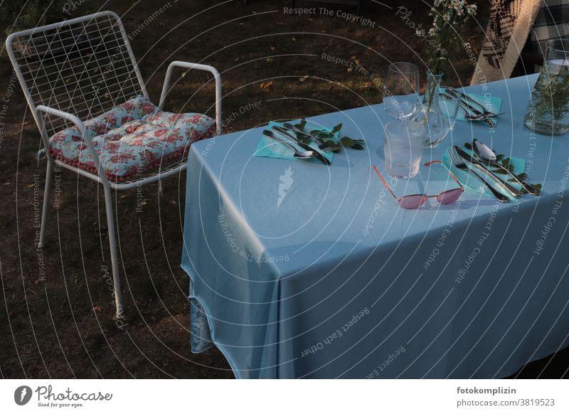 gedeckter Gartentisch mit blauer Tischdecke, Gartenstuhl, Blumenkissen und Sonnenbrille Gartenleben Gartenmöbel Sommerfest gedeckter Tisch gemeinsam Laube