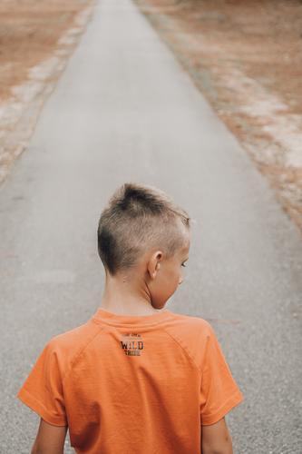 Kind von hinten mit orangem T-Shirt auf einer Straße Unschuld orange Farbe Stil inspirierend Männer Jungen eine Person Rückansicht Kindheit Lebensstile