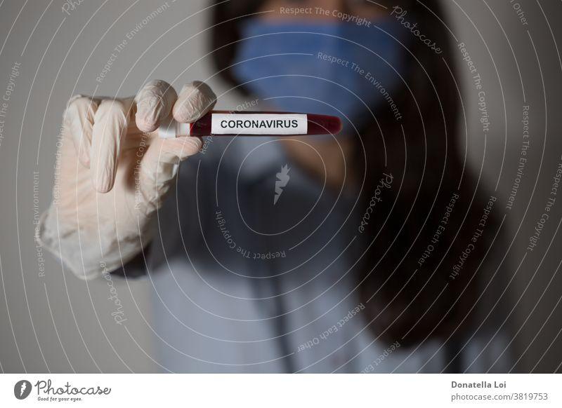 Person hält ein Reagenzglas mit Coronavirus-Inschrift Blut Pflege Klinik Nahaufnahme Konzept COVID19 Arzt Seuche Frau Mädchen Glas Handschuhe Hände Gesundheit