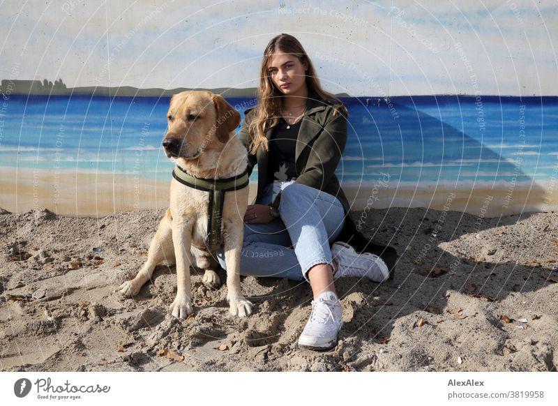 Blondes Mädchen und eine blonder Labrador sitzen an einer Wand mit Graffiti am Strand Landschaft intensiv jugendlich freundlich Natur weiblich einzigartig