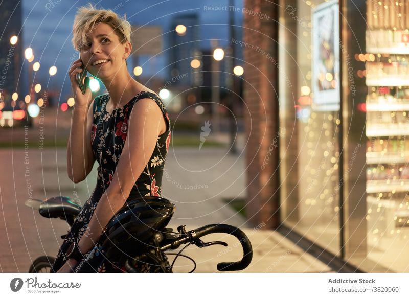 Junge Frau spricht am Telefon in der Nähe von Geschäft und Fahrrad Kleid Abend Spaziergang Mädchen jung Reiten schön Großstadt Nacht Lichter Gebäude Glas
