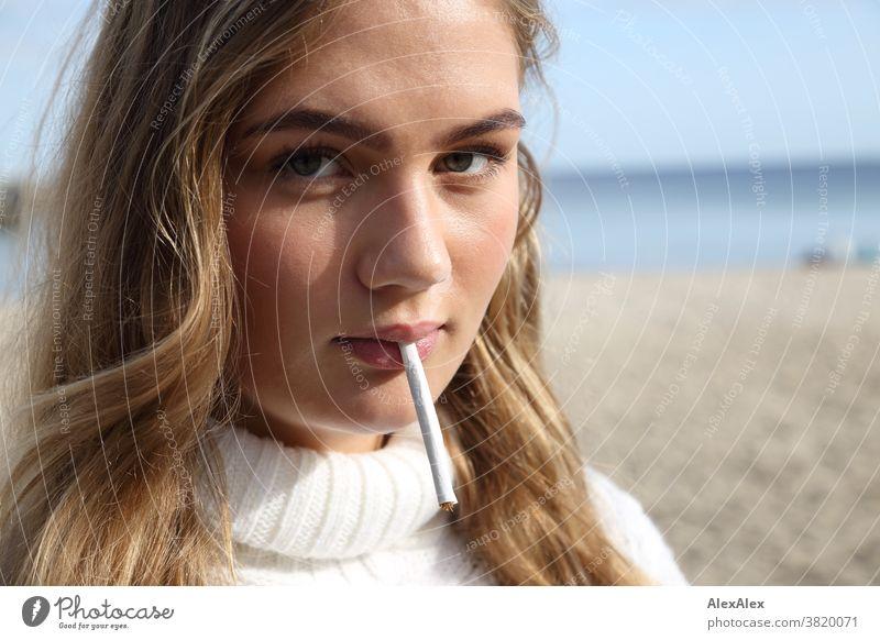 Blondes Mädchen steht am Ostessestrand und hat eine selbstgedrehte Zigarette im Mund Landschaft Strand intensiv jugendlich freundlich Natur weiblich einzigartig