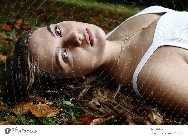 Seitliches Portrait eines Mädchen in weißem Trägertop das auf einer Herbstwiese mit Laub liegt Landschaft Strand intensiv jugendlich freundlich Natur weiblich