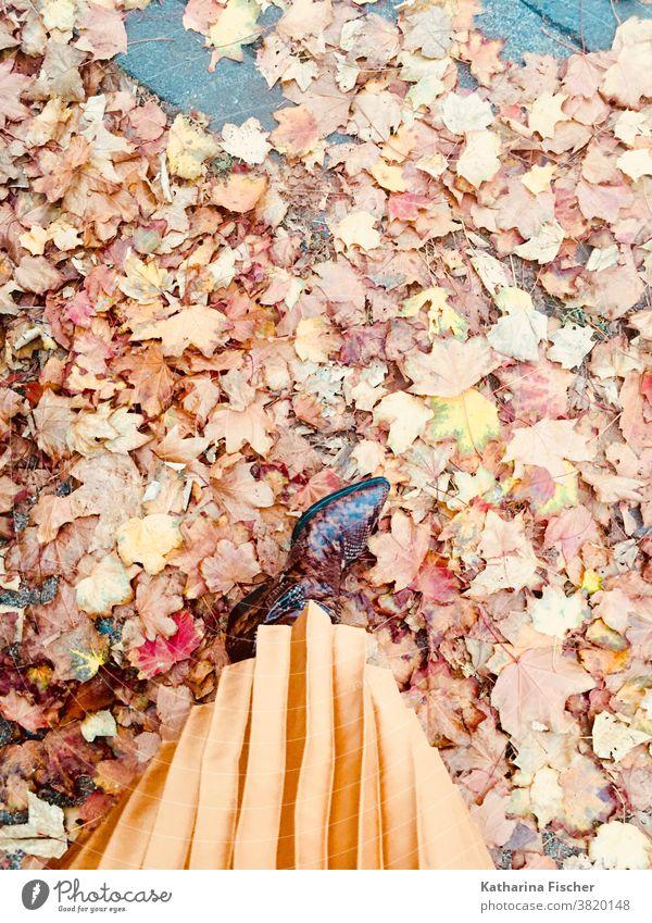 Herbstimpressionen, Lederstiefel und Plisseerock auf Herbstlaub Vogelperspektive Schuhe Außenaufnahme Tag Fuß Beine Farbfoto Bodenbelag rot stehen Straße braun