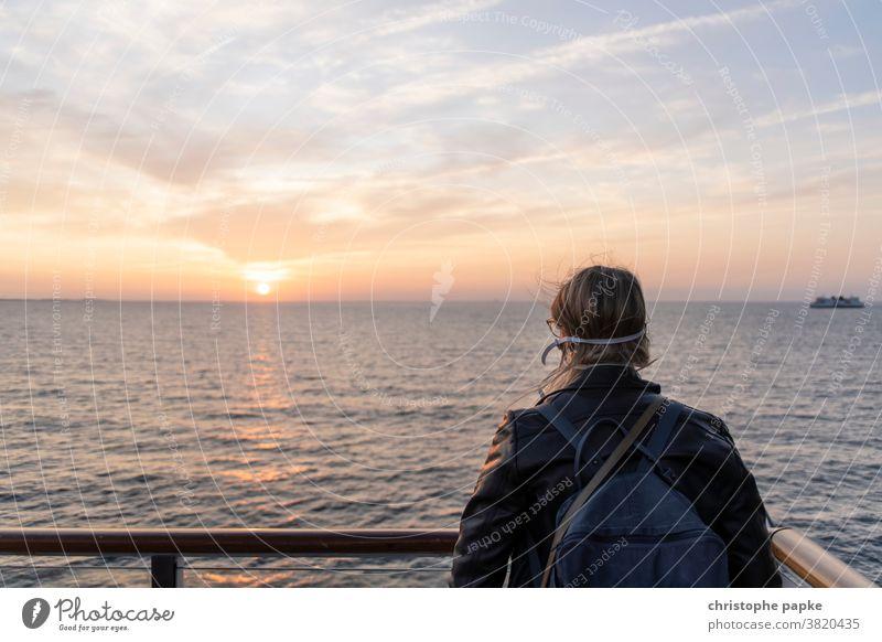 Frau mit Mund-nasen-schutz schaut auf Meer mund-nasen-schutz reisen Mundschutz Pandemie Sonnenuntergang Maske Corona Infektionsgefahr Corona-Virus COVID