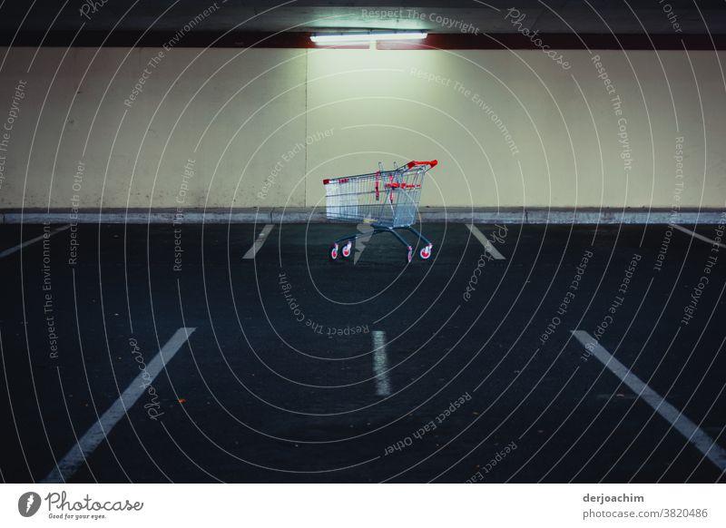 Ein Einkaufswagen aus Metall, mit roten Griffen  steht einsam verlassen in der Tiefgarage vor einer hellen Mauer. Er ist aber ganz vorschriftmäßig in der Parkbucht zwischen den weißen Makierungen abgestellt. Eine einsame Leuchtstoffröhre erhellt das ganze