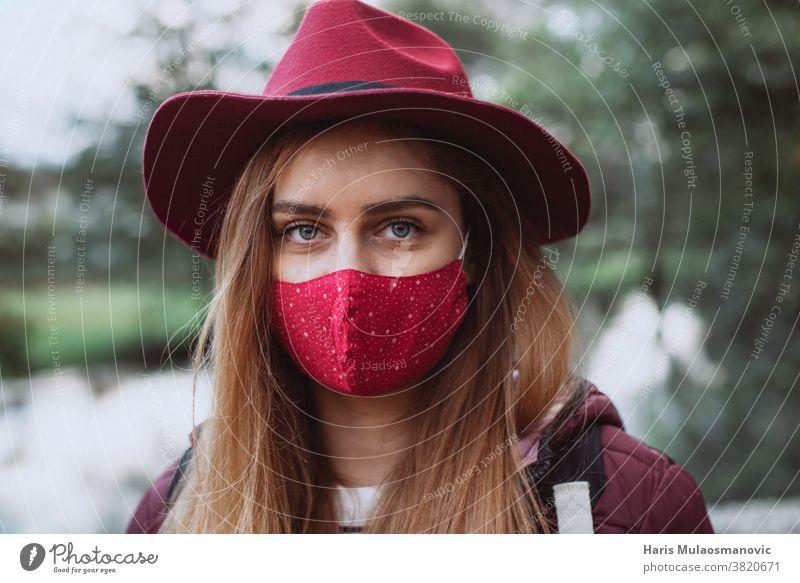 Schöne Frau mit rotem Hut und Gesichtsmaske in Nahaufnahme Erwachsener attraktiv schön Schönheit Kaukasier abschließen kalt Coronavirus covid-19 niedlich Mode