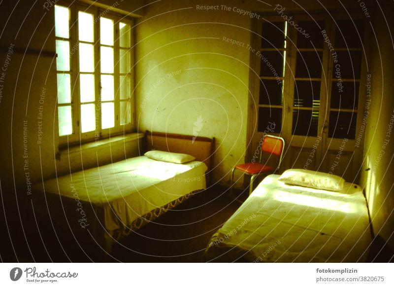 leeres karges Hotelzimmer mit zwei Betten und rotem Stuhl Trip Tourism fremde länder Nostalgie nostalgisch vintage Urlaub Backpacking reiselust Reise reisen
