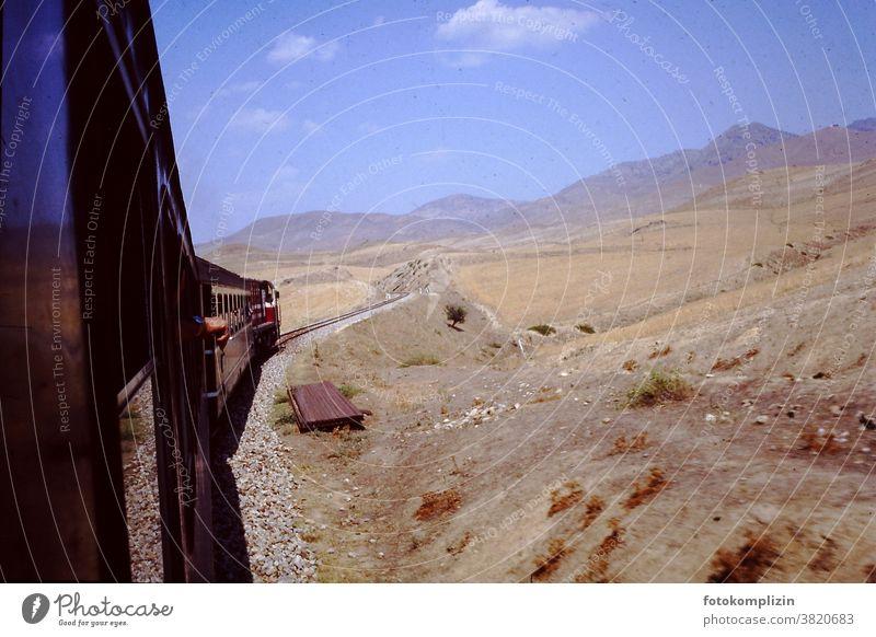 Blick aus fahrendem Zug in eine trockene bergige Landschaft zug Zugfahrt alt retro Wüste Steppe heiß Süden Ferne Weite Bahnfahren unterwegs sein Tour Reise