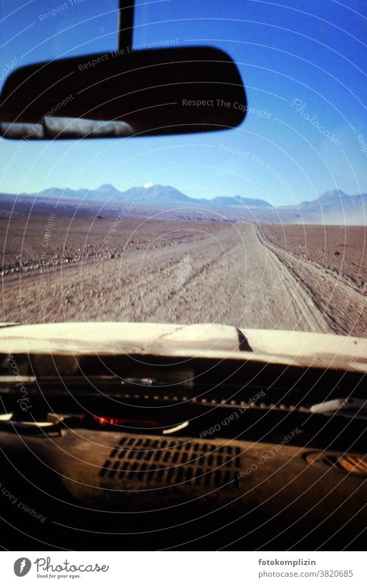 Cockpit eines alten Autos mit Blick nach vorne auf eine Wüstenpiste reisen Autospiegel Piste wüst Menschenleer Chile Wüstenberge Ferne Landschaft Nostalgie