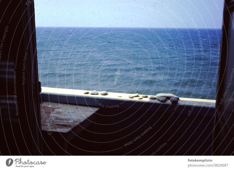 Meer Sehnsucht Blick auf das Meer Balkonbrüstung Steine Kieselsteine retro altehrwürdig Meerblick Wasser Urlaub sehnsucht Fensteraussicht Erholung Sommer Sonne