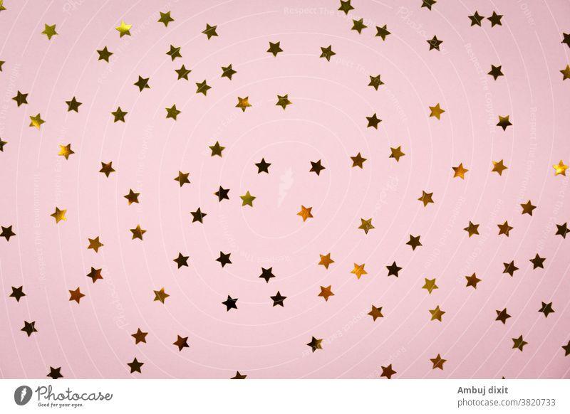 Speichern Download Vorschau herunterladen Goldener Stern streut auf rosa. Festlicher Feiertagshintergrund. Konzept einer Feierlichkeit. Draufsicht, flach gelegt. Waagerecht