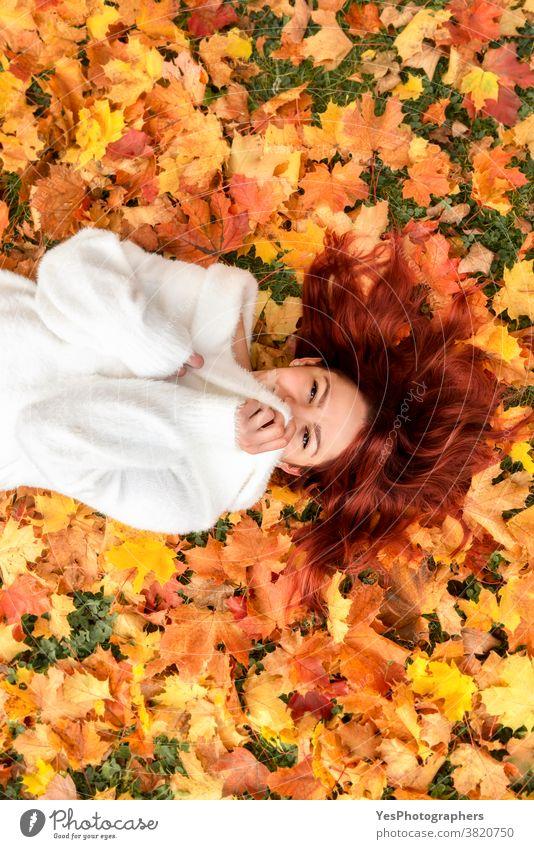 Schöne rothaarige Frau auf Herbstlaub liegend. Junge Frau lächelt in Herbstlandschaft 20s November Oktober obere Ansicht Erwachsener allein Herbstmode