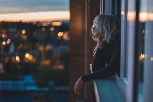 Porträt einer kaukasischen Frau, die zur blauen Stunde am Fenster lehnt. blond Sternstunde Zauberei u. Magie Farbfoto Blick Mensch Mode Lifestyle Stil Bokeh