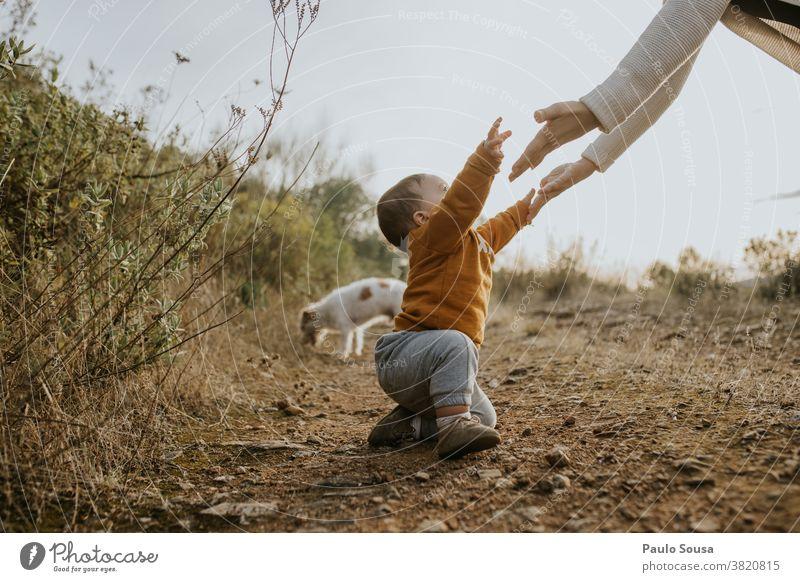 Kleinkind hebt die Hand zur Mutter Kaukasier 1-3 Jahre Erhöhung Zusammensein Zusammengehörigkeitsgefühl Eltern Lifestyle Fröhlichkeit Familie & Verwandtschaft