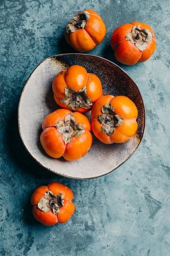 Köstliche Kakipflaume in einem Teller auf blauem Hintergrund süß frisch saftig Gesundheit orange Lebensmittel organisch Diät reif Vegetarier Frucht Ernährung