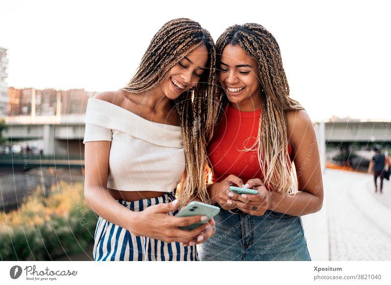 Glückliche Schwestern telefonieren per Telefon Tippen Lächeln Vorderansicht Afroamerikaner Zopf Straße attraktiv jung Stil Ausdruck schön hübsch ethnisch