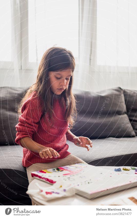 Ein wunderschönes kleines Mädchen, das mit den Fingern auf einer Leinwand keucht. Farben Kindheit Lächeln Kunst lustig Spaß zeichnen Kreativität Lernen Glück