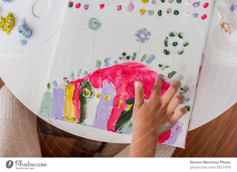 Hände eines kleinen Mädchens, das mit den Fingern in einer Leinwand keucht. Farben Kindheit Lächeln Kunst lustig Spaß zeichnen Kreativität Lernen schön Glück