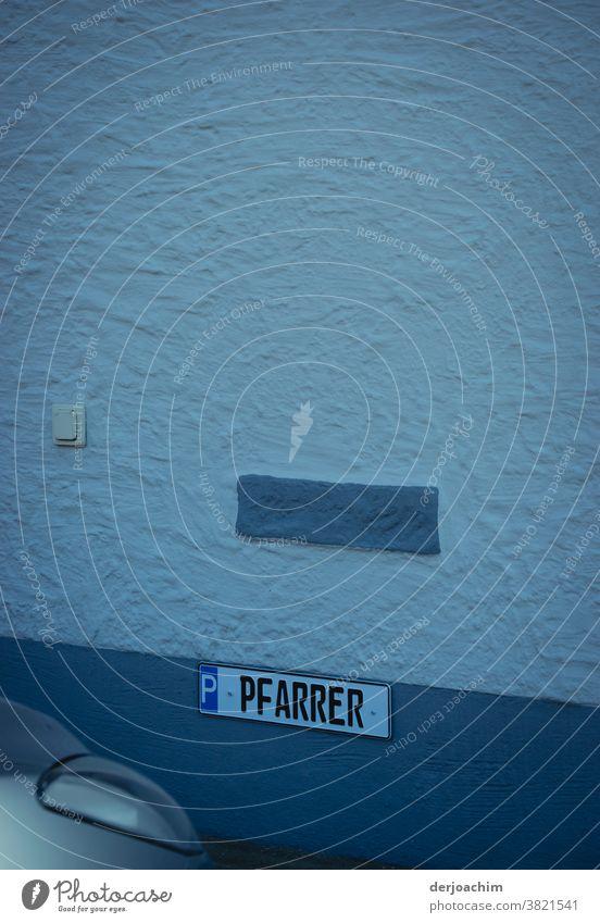 Parkplatz für den PFARRER. Der ist leider von einem unbekannten PkW besetzt. Das Schild ist an einer weißen mit blau abgestuften Wand befestigt . Im unteren Bildrand links, ist ein Scheinwerfer zu erkennen.