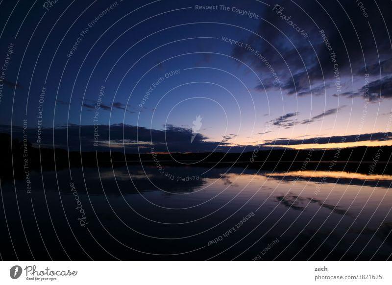 Der Tag geht leuchten Dämmerung Wasser See Sonnenuntergang Sommer Reflexion & Spiegelung Wolken blau Seeufer Licht ruhig Himmel Natur Landschaft Erholung