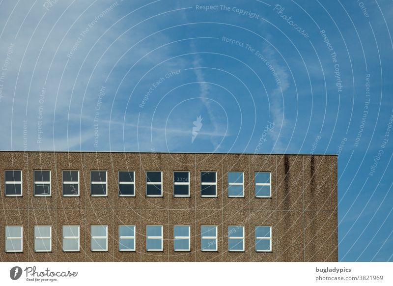 Gebäude aus Waschbeton mit vielen Fenstern vor blauem Himmel mit Wolken und Kondensstreifen Architektur Haus Beton Glasfenster Fassade Bauwerk grau trist