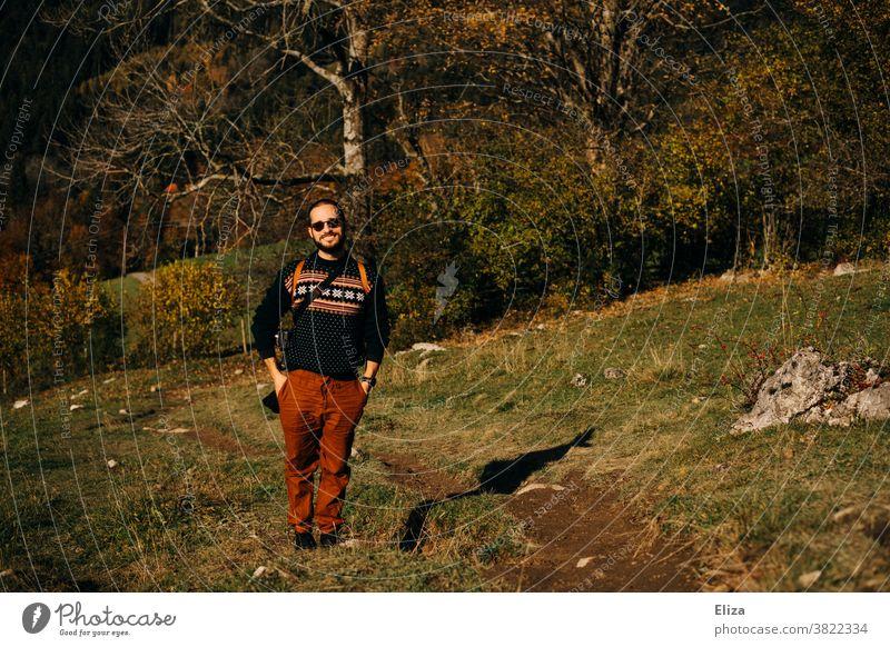 Ein junger Mann steht in einer herbstlichen Landschaft und lächelt Natur Herbst Ausflug Wandern Sonnenschein goldener Herbst Schönes Wetter Wald Wiese