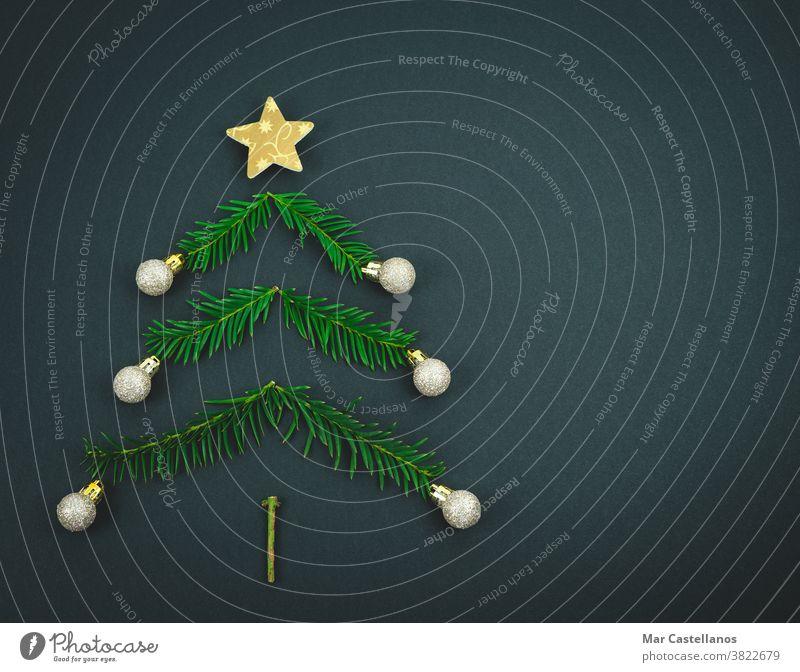 Weihnachtsbaum aus Kiefernzweigen auf schwarzem Hintergrund. Dekoration & Verzierung Weihnachten Ende des Jahres Baum Niederlassungen Stern Bälle
