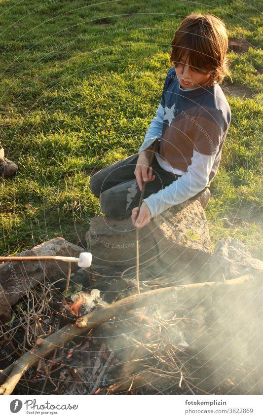 Kind am Lagerfeuer beim Marshmallows grillen Schaumzucker lecker süß Rauch Feuerstelle Junge Grillen Kindererziehung Kindheitserinnerung Natur draußen sein