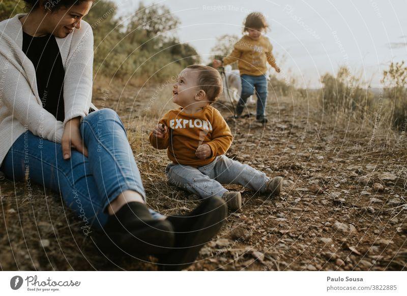 Mutter mit zwei Kindern, die im Freien spielen Familie & Verwandtschaft Muttertag Mutterschaft Geschwister Kleinkind Natur authentisch Lifestyle Leben Kindheit