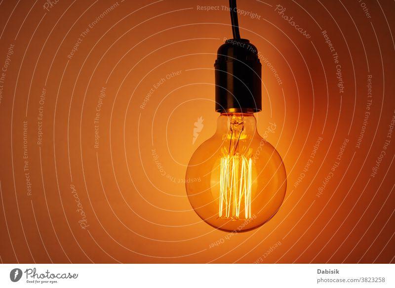 Vintage-Glühbirne auf orangefarbenem Hintergrund, Kopierfeld. Glühende Edison-Glühbirne Knolle Licht altehrwürdig Lampe Design weiß kreativ Konzept Idee Farbe