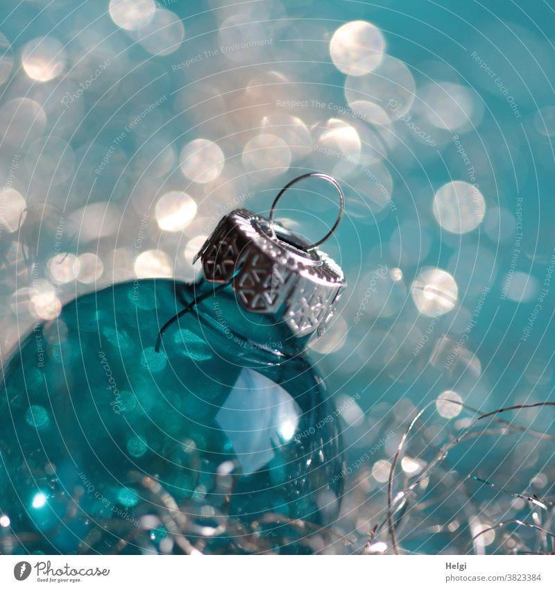 Weihnachtsglitzern - türkisblaue Weihnachtskugel aus Glas mit silbernem Aufhänger vor türkis-weißem Hintergrund mit Bokeh Glaskugel Dekoration Weihnachtsschmuck